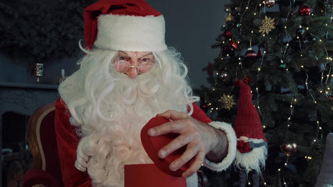 Close up portret Santa Claus opens magic glowing gift box and looks inside Live Action