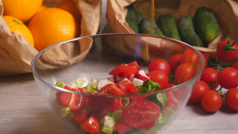 Adding olive oil to vegetable salad of tomatoes, cucumber and lettuce Live Action