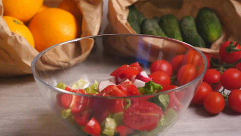 Preparing vegetable salad of tomatoes, cucumber, lettuce and radish Live Action