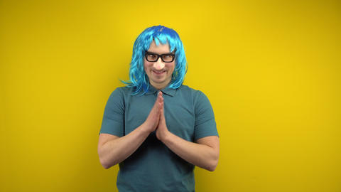 A funny young man in a female blue wig and glasses with a nose rubs his hands Live Action