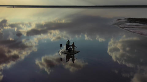 Three musicians are floating in the sea near the shore on a raft, reflection, 4k Live Action
