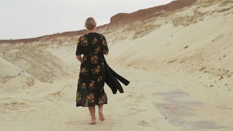 Back view of barefoot woman walks in desert Live Action