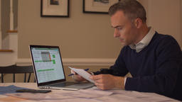 a man going over his bills on his dining room table Footage