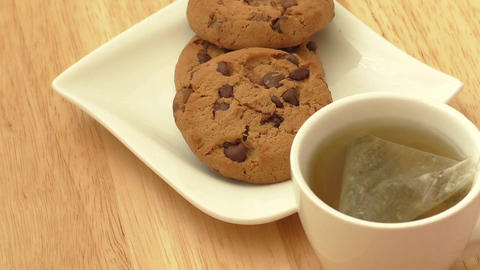 Cup of tea with tea bag and cookies Footage