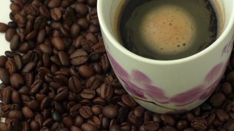 White coffee cup with coffee and around the cup lies coffee beans Footage