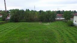 Flight over men mowing hay Footage