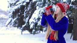 Lovely woman in winter clothes enjoying hot drink Footage