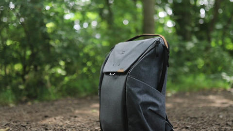 Peak Design Gray backpack for photography equipment on a dirt path in a park Live Action