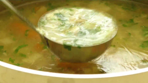 Homemade chicken soup in pot with carrots Live Action