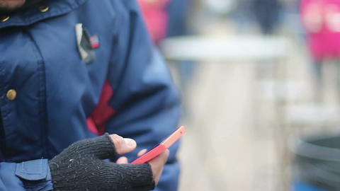 Male hand in old fingerless gloves using touch phone, poor man texting message Footage
