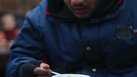 Hungry pauper eating food donated by volunteers, charity event for poor people Live Action