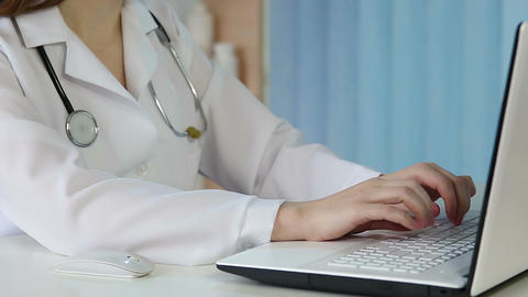 Female doctor working on laptop in office, clicking mouse, typing on keyboard Footage