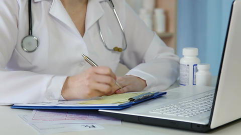Doctor writing medical prescription, checking clinical records, signing papers Footage