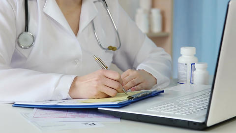 Female physician making records, writing medical prescription, filling in forms Footage