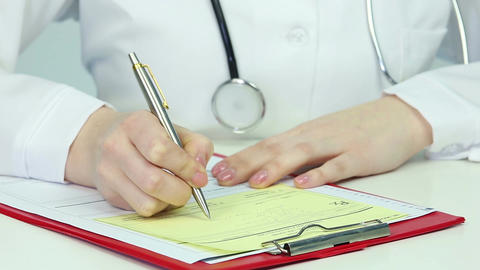 Close-up of female doctor's hands writing prescription and giving it to patient Footage
