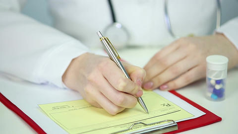 Female physician working in office, filling out Rx prescription form, reception Footage