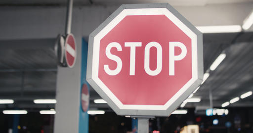 Red stop sign blinking in an empty garage at night Live Action