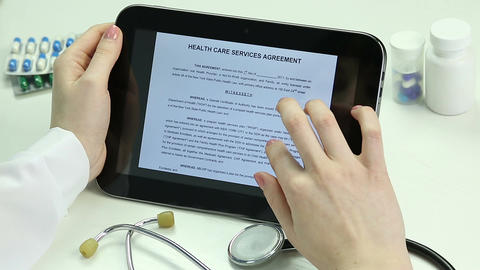 Doctor reading agreement, studying documents on tablet. Electronic documentation Footage