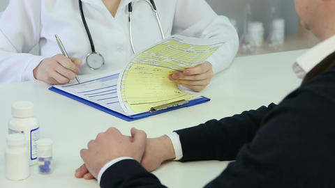 Health specialist writing diagnosis and prescription in patient's medical record Footage