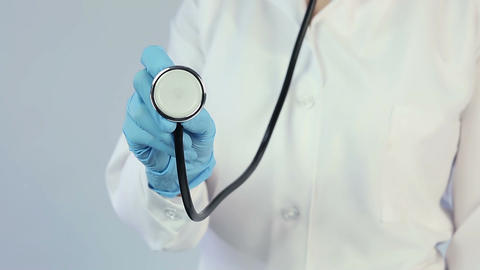 Doctor in lab coat and medical gloves holding out stethoscope to camera, clinic Footage