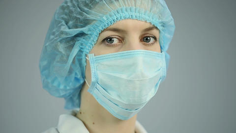 Female surgeon looking into camera with sad eyes, preparing to tell bad news Footage