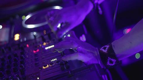 Stylish DJ performing modern music behind console, entertaining public in club Footage
