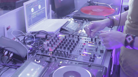 Timelapse of DJ switching controls, performing music on sound board in nightclub Footage