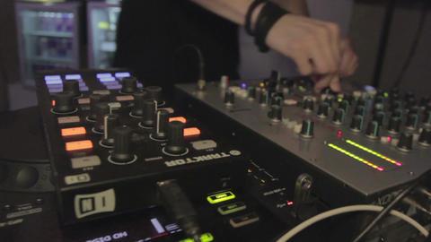 DJ dancing near audio mixer and performing music. Man enjoying his work. Party Footage