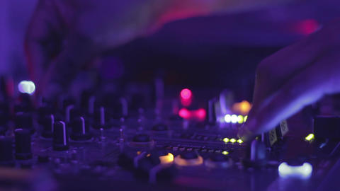 DJ hands pushing buttons on the mixing console. Night club atmosphere. Party Footage