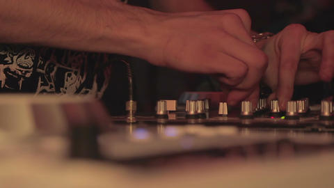 Deejay's hands pushing and turning buttons on the mixing console. Nightclub Footage