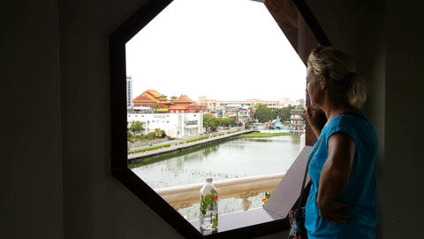 European blond woman looking through window on the Tiger pagoda Footage