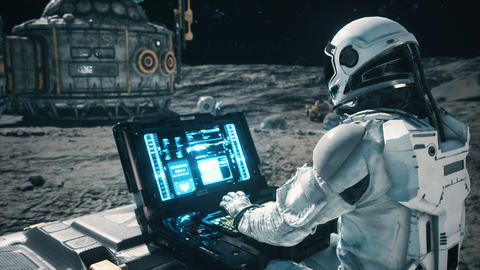 An astronaut works on his science laptop in a space colony on one of the planets. Looping Animation Animation