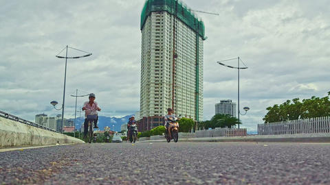 Scooters Drive along Paved Street Road against Skyscraper Footage