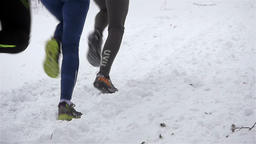 Slow motion: legs of three winter runners on a snow covered forest trail ビデオ