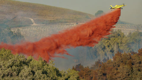 Fire fighter plane drops fire retardant on a forest fire 4 Live Action