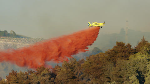 Fire fighter plane drops fire retardant on a forest fire 2 Live Action