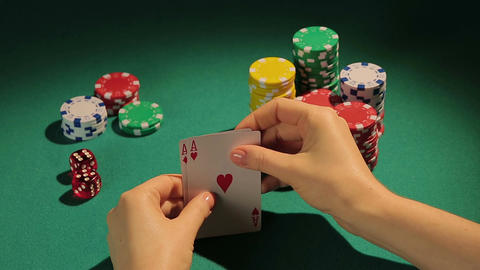 Fortunate poker player checking cards, getting chance to win game with two aces Footage
