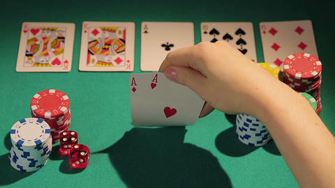 Poker player catching full house hand, checking cards before betting chips Footage