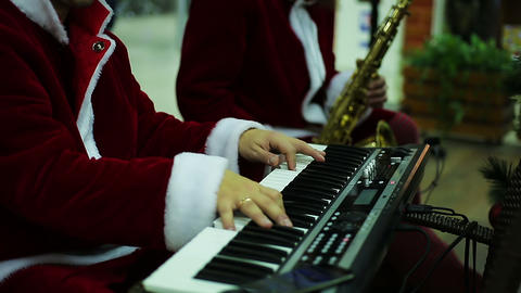 Musical band in Santa Claus suits playing merry melody to create Xmas atmosphere Footage