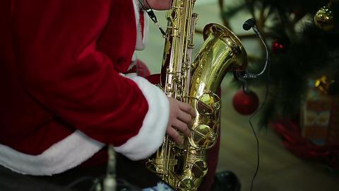 Man wearing Santa suit playing Xmas carol song on saxophone at festive concert Footage