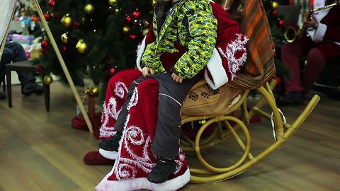 Cheerful kid sitting on Santa Claus knees to make Xmas wish, happy childhood Footage