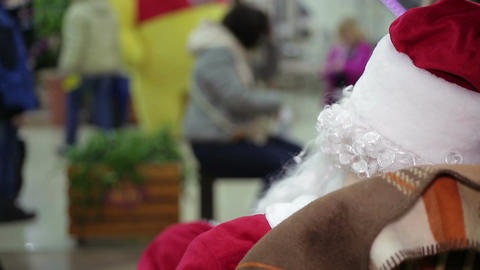 Back view of Santa Claus looking at busy passers-by in crowded trade center Footage