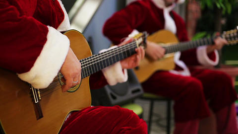 Male guitarists in Santa suits playing joyful songs at Christmas eve concert Footage