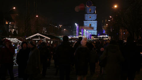 Crowd of people walking down central street, enjoying Christmas festivities Footage