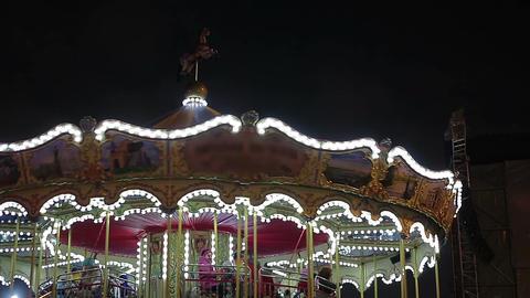 Happy children enjoying ride on merry-go-round with parents, amusement park Footage