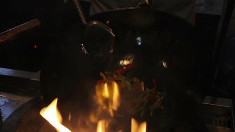 Professional cook grilling and stirring vegetables in the pan. Asian food fest Footage