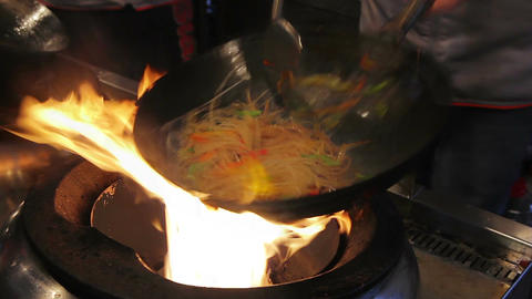 Street cook frying tasty noodles and vegetables in sauce. Professional cooking Live Action