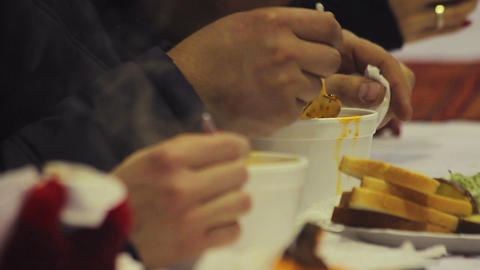 Charity event. Helping homeless. Poor and hungry people eating hot tasty soup Footage