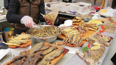 Street food seller putting crispy salty anchovies in package. Appetizing snacks Footage