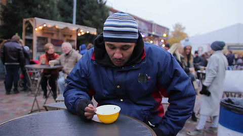 Hungry man eating tasty soup at street food festival. Loneliness and sadness Footage